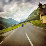Biker race across mountainous village Stock Photo