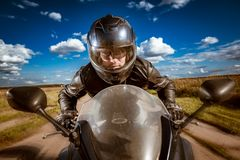 Biker racing on the road stock images