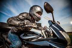 Biker racing on the road. Biker in helmet and leather jacket racing on the road Stock Images