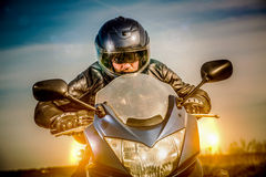 Biker racing on the road Stock Photography