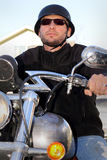 Biker Ready to Ride. An unshaven biker wearing a German Kaiser style helmet and sunglasses ready to ride bike. Shallow depth of field Stock Photos