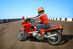 Biker and red motorcycle Stock Image