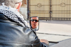 Biker reflecting in rear view mirror. Vertical color portrait of face reflection of a Caucasian motorbiker in a rear view mirror waiting at car park gates to Royalty Free Stock Image