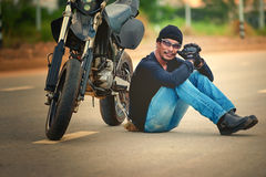 Biker relax sitting with motorbike on road in sunset Royalty Free Stock Photography
