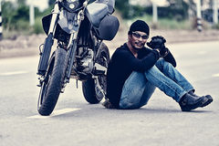 Biker relax sitting with motorbike on road in sunset Stock Image