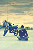 Biker relax sitting with motorbike on road in sunset Royalty Free Stock Photos