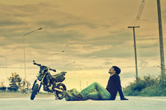 Biker relax sitting with motorbike on road in sunset Royalty Free Stock Image