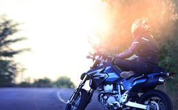 Biker relaxes on his motor bike. Motorcyclist yogi sits on a motorcycle in a lotus pose royalty free stock image