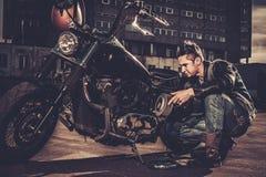 Biker repairing his custom motorcycle bobber Stock Image