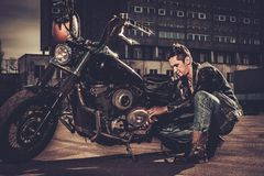 Biker repairing his custom motorcycle bobber stock image