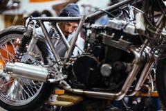 Biker repairing Motorcycle in Garage. Portrait of bearded long-haired man working in garage customizing motorcycle and repairing broken parts stock image