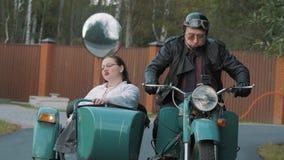 Biker ride in suburbs motorcycle with woman nurse costume grimacing in sidecar stock video