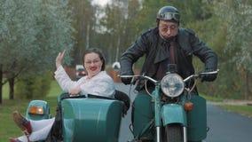 Biker ride in village motorcycle with woman nurse costume grimacing in sidecar stock footage