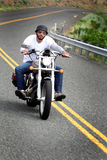 Biker Rides Curvy Road. An unshaven biker wearing a German Kaiser style helmet and sunglasses happily riding his bike in hill country on a curvy road. Shallow royalty free stock image