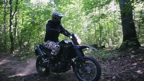 A biker rides his motorcycle into the sunlight on the forest trail, motocross ATV. A Caucasian man in a sports protective suit and helmet rides a black stock footage