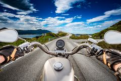 Biker rides a road with Atlantic Ocean Road in Norway. First-per Royalty Free Stock Image