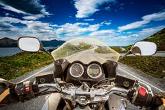 Biker rides a road with Atlantic Ocean Road in Norway. First-per. Son view Royalty Free Stock Image