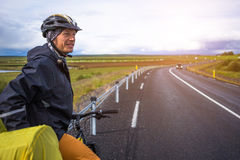 Biker rides on road at sunny summer day in Iceland. Happy man during bicycles trip in Iceland Stock Image