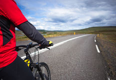Biker rides on road at sunny summer day in Iceland. Happy man during bicycles trip in Iceland Stock Photography
