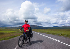 Biker rides on road at sunny summer day in Iceland. Happy man during bicycles trip in Iceland Royalty Free Stock Photos