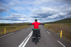 Biker rides on road at sunny summer day in Iceland. Happy man during bicycles trip in Iceland Royalty Free Stock Image