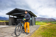 Biker rides on road at sunny summer day in Iceland. Travel and sport picture Stock Photos