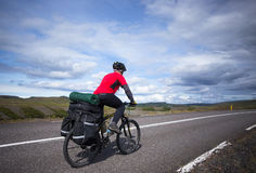 Biker rides on road at sunny summer day in Iceland. Travel and sport picture Stock Image