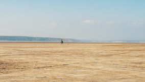 Biker riding along sandy beach. Motorcyclist rides motorcycle through desert. stock video