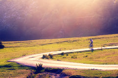 Biker riding on country road Royalty Free Stock Photography