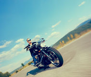 Biker riding a customized motorcycle. On an open road shot with a tilt and shift lens and with very shallow depth of field Royalty Free Stock Image