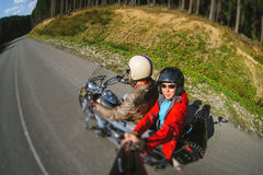 Biker riding his motorcycle on the road with the passenger. Biker and passenger are riding motorcycle on the road with high speed. Biker is wearing leather Stock Photo