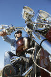 Biker Riding Motorcycle Against Clear Sky. Low angle view of male biker riding motorcycle against clear sky stock photography
