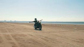 Biker riding motorcycle hands free on sandy beach through desert. stock video footage