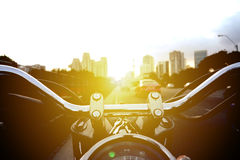 Biker riding motorcycle on traffic road at sunny day. Men ride biker on the road. Bike riding on a motocycle view of front motobike on sunset Royalty Free Stock Photos