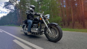 A biker riding a motorcycle wearing black clothes and helmet. stock video