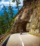 Biker riding into mountainous tunnel Stock Photo