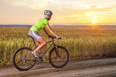 Biker riding rural road against sunset Stock Photography