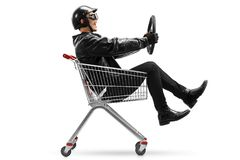 Biker riding in shopping cart and holding steering wheel Royalty Free Stock Image