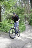 Biker riding on  summer forest trail Royalty Free Stock Photography