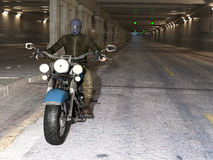 Biker riding in a tunnel. Young handsome biker riding motorcycle through the twilight tunnel. 3d render Royalty Free Stock Photos