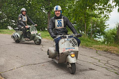 Biker riding a vintage scooter Vespa. Biker riding a vintage italian scooter Vespa Piaggio in rally of classic Vespa of the forties - fifties Trofeo dell' Stock Photo