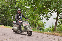Biker riding a vintage scooter Vespa. Biker riding a vintage italian scooter Vespa Piaggio in rally of classic Vespa of the forties - fifties Trofeo dell' Stock Photos