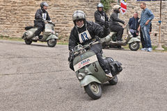 Biker riding a vintage scooter Vespa. Biker riding a vintage italian scooter Vespa Piaggio in rally of classic Vespa of the forties - fifties Trofeo dell' Royalty Free Stock Images