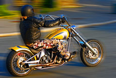 Biker on the road. Motorbiker down the road in the evening sun Royalty Free Stock Image
