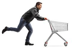 Biker running and pushing an empty shopping cart Stock Image