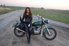 Biker sexy girl sitting on vintage custom motorcycle. Outdoor lifestyle toned portrait. Biker sexy woman sitting on vintage custom motorcycle. Outdoor lifestyle royalty free stock image