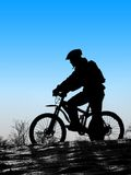 Biker silhouette. Mountain biker silhouette with clean blue sky Royalty Free Stock Images
