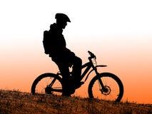 Biker silhouette. Mountain bike racer silhouette in orange sunrise royalty free stock photos