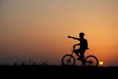 Biker silhouette. Mountain biker silhouette in sunrise royalty free stock photography