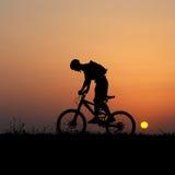 Biker silhouette. Mountain biker silhouette in sunrise royalty free stock photo